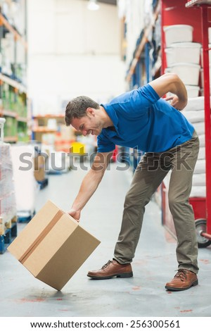 Side view of worker with backache while lifting box in the warehouse - stock photo