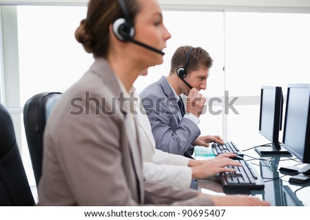 Side view of working call center agents - stock photo