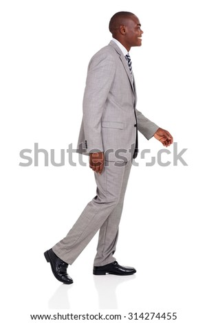 side view of young african american businessman walking