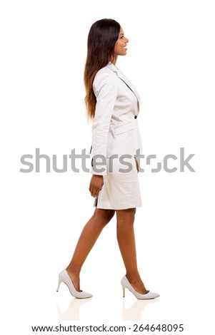 side view of young african american businesswoman walking on white background - stock photo