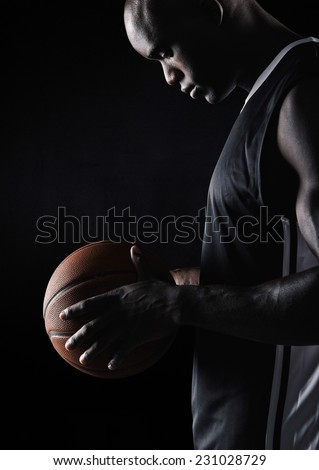 Side view of young african sportsman holding basketball against black background. Basketball player with ball. - stock photo