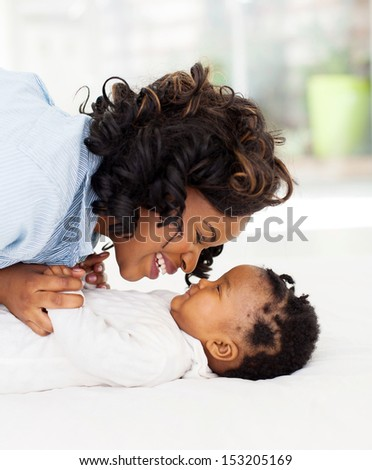 side view of young African woman playing with her little baby in bed - stock photo