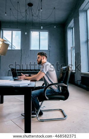 Side view of young bearded businessman working on laptop at desk in old grunge office