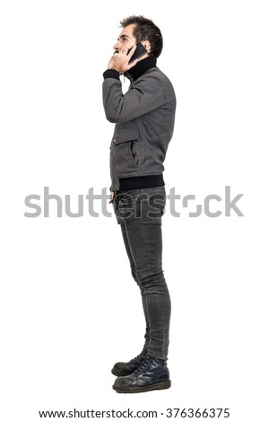 Side view of young bearded man in gray jacket talking on the mobile phone. Full body length portrait isolated over white studio background.  - stock photo