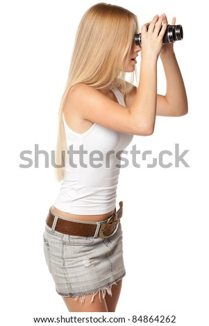 Side view of young beautiful female looking through binocular in distance over white background