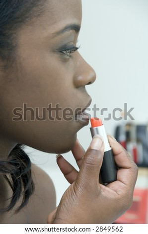 Side view of young black woman applying gloss to her lips