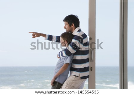 Side view of young boy with father pointing out to sea in doorway - stock photo