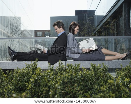 Side view of young businessman and businesswoman reading newspapers while sitting back to back on wall - stock photo