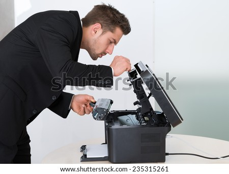 Side view of young businessman fixing cartridge in photocopy machine at office - stock photo