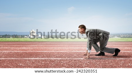 Side view of young businessman in start position on track - stock photo