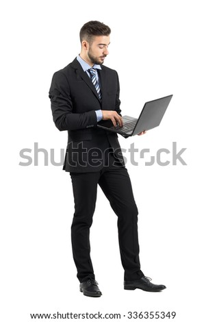 Side view of young businessman in suit using laptop.  Full body length portrait isolated over white studio background.  - stock photo