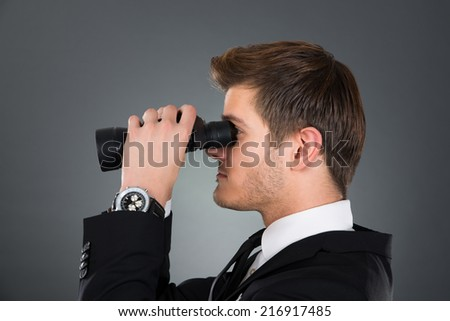 Side view of young businessman looking through binoculars against gray background - stock photo