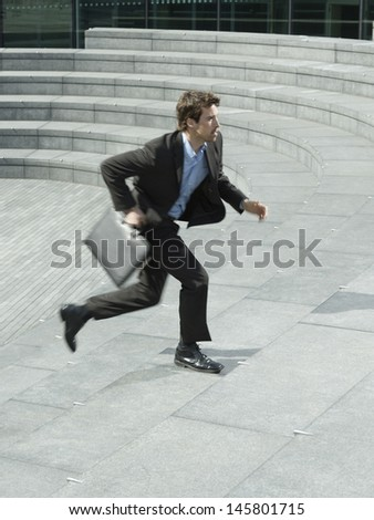 Side view of young businessman with briefcase running upstairs outdoors - stock photo