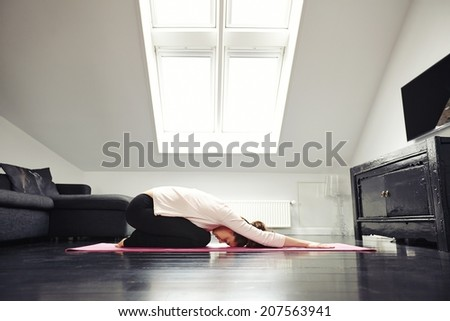 Side view of young caucasian woman exercising yoga in her living room. Female doing relaxation exercise on mat at home. - stock photo