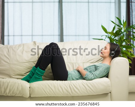 side view of young caucasian woman lying on sofa and listening to music with headphones - stock photo