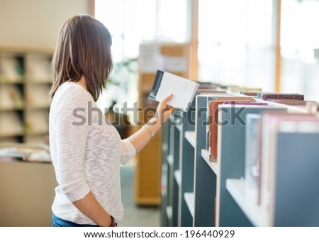 Side view of young college student reading book in library - stock photo