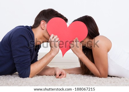Side view of young couple hiding behind heart shape while lying on rug at home - stock photo