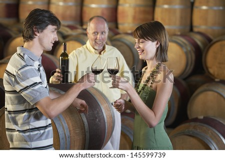 Side view of young couple toasting red wine with merchant in background - stock photo