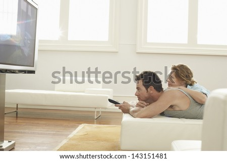 Side view of young couple watching TV at home - stock photo