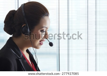 Side view of young female call center representative in office - stock photo