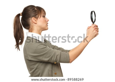 Side view of young female looking with magnifying glass, over white background - stock photo