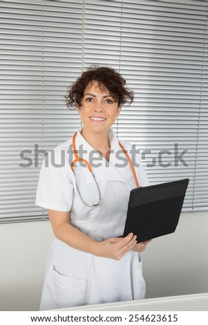 Side view of young female surgeon using digital tablet