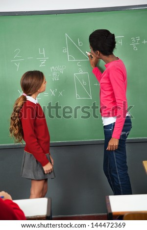 Side view of young female teacher teaching mathematics to teenage schoolgirl in classroom - stock photo