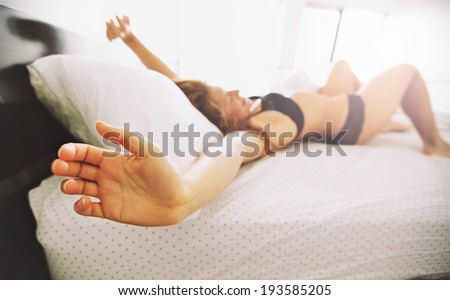 Side view of young female waking up. Young woman in lingerie stretching her arms while lying in bed. Morning stretch. - stock photo