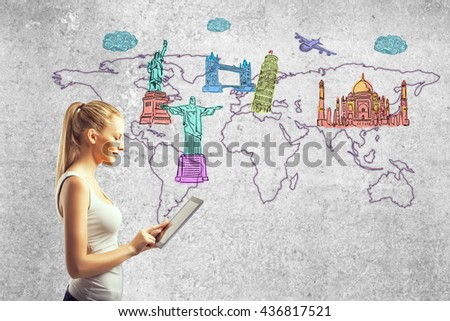 Side view of young girl using tablet against concrete wall with map and sights sketches. Travel concept - stock photo