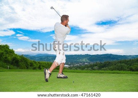 Side view of young golfer in swing pose.
