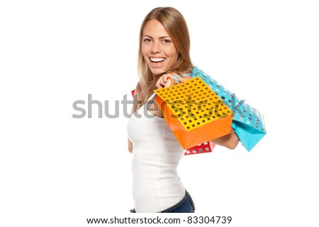Side view of young happy female holding shopping bags with purchases over white background - stock photo