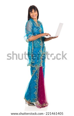 side view of young indian woman in saree using laptop - stock photo