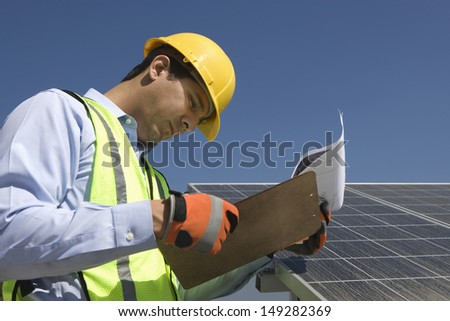 Side view of young maintenance worker looking at clipboard near solar panels - stock photo