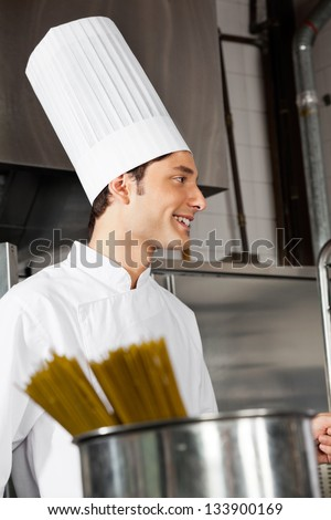 Side view of young male chef standing in industrial kitchen
