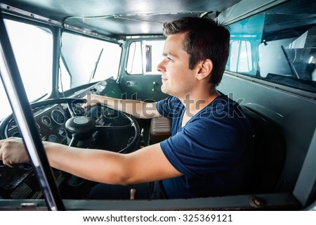 Side view of young male firefighter driving truck at fire station - stock photo