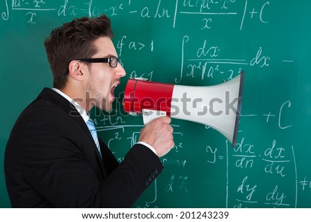 Side view of young male professor screaming on megaphone against blackboard - stock photo