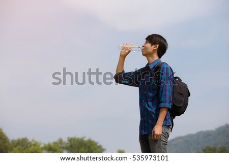 Side view of young man drinking water while standing at outdoors.