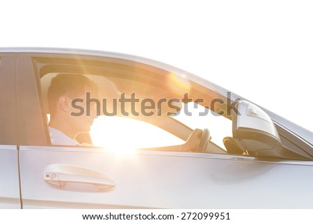 Side view of young man driving car - stock photo