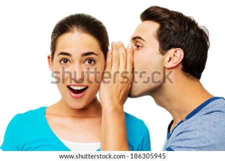 Side view of young man sharing secret with surprised woman over white background. Horizontal shot.