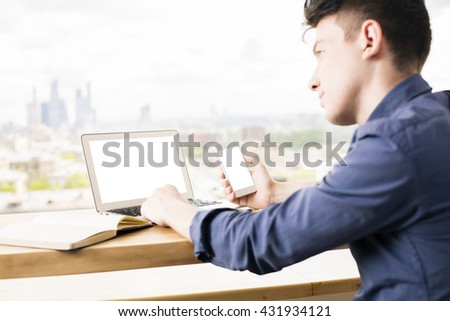 Side view of young man using laptop and smart phone with blank white screen on wooden desktop. Blurry city background. Mock up