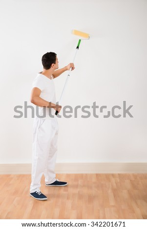 Side view of young man using paint roller on white wall at home - stock photo