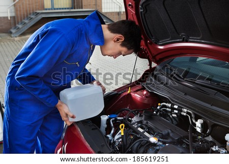 Side view of young mechanic pouring antifreeze into windscreen water tank on street - stock photo