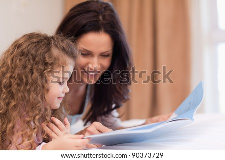 Side view of young mother and daughter reading a book together
