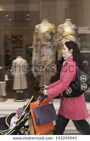 Side view of young mother pushing baby stroller by clothes shop - stock photo