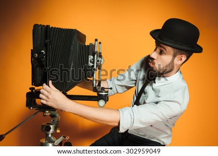 side view of young positive man in hat as photographer with retro camera on an orange background - stock photo