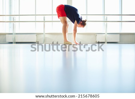 Side view of young sportsman doing physical exercises in gym