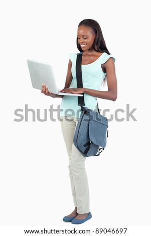 Side view of young student with her laptop against a white background - stock photo