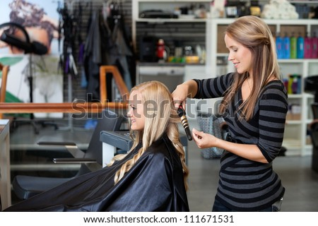 Side view of young stylist curling woman's hair giving a new hairstyle at hair salon