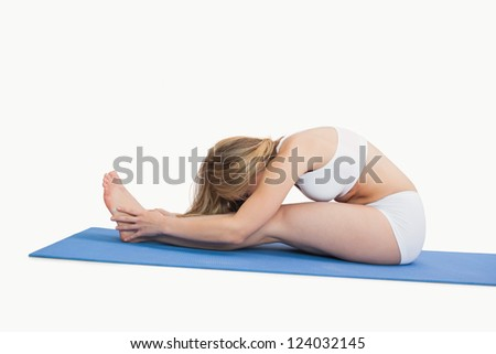 Side view of young woman doing the paschimottanasana pose over white background - stock photo