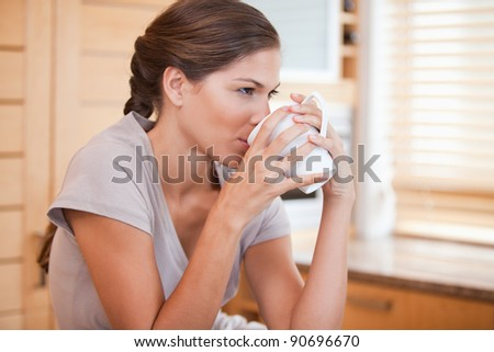 Side view of young woman drinking coffee - stock photo